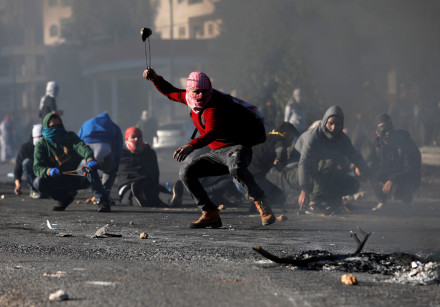 A Palestinian hurls stones toward Israeli troops in response to US recognition of Jerusalem