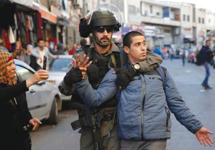 An Israeli border police officer detains a Palestinian protester  demonstration in east Jerusalem