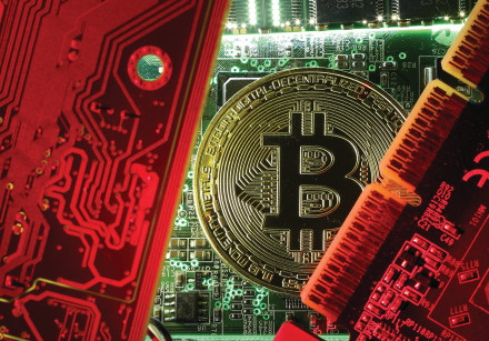 A coin representing the bitcoin cryptocurrency is seen on computer circuit boards in this illustrat