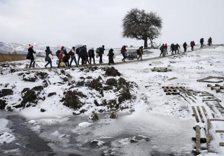 Migrants cross a snowy field, January 2016