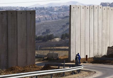 Palestinians walk near an opening in Israel's barrier in east Jerusalem