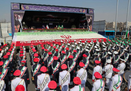 Iranian President Hassan Rouhani gestures as members of Iranian armed forces take part in a rally ma