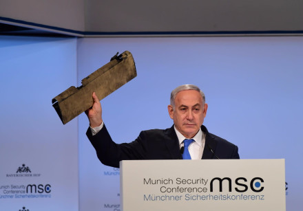Prime Minister Benjamin Netanyahu holds up part of Iranian drone that landed in Israel in February 2