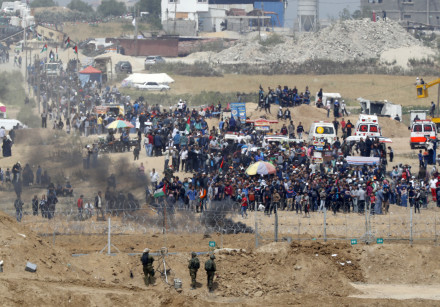 Israeli soldiers keeping position and Palestinian protestors gathering along the border fence