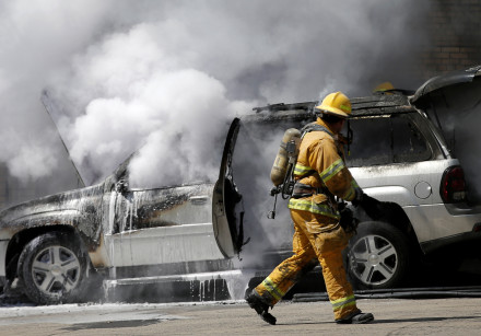A firefighter approaches a burning car in New York City