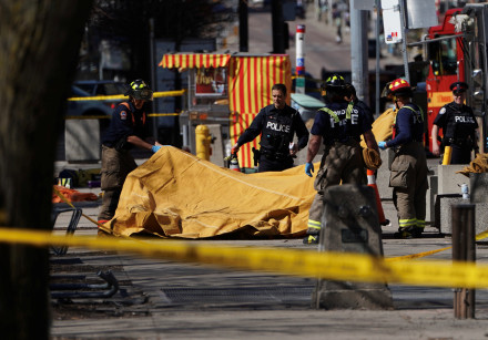 Firemen cover a victim of an incident where a van struck multiple people at a major intersection in