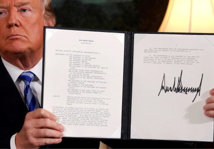 US President Donald Trump holds up a proclamation declaring his intention to withdraw from the JCPOA