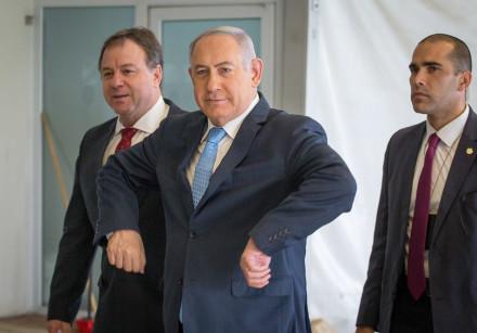 Prime Minister Benjamin Netanyahu gestures chicken wings as he enters a cabinet meeting.