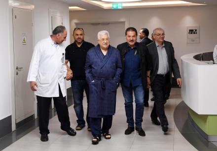 Palestinian President Mahmoud Abbas walks inside the hospital in Ramallah