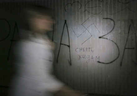 A woman walks past a swastika and the inscription