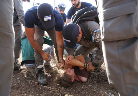 Security forces arrest an activist during the eviction of Tapuach West, June 17th, 2018
