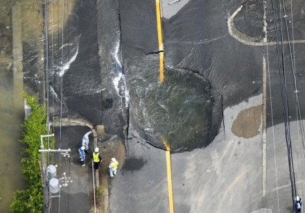 Water flows out from cracks in a road damaged by an earthquake in Takatsuki, Osaka prefecture, weste