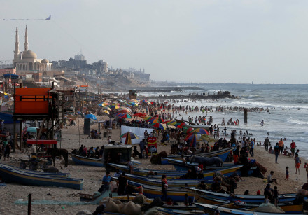 Gazans swim in the Mediterranean Sea as others enjoy their time on a beach in the northern Gaza Stri