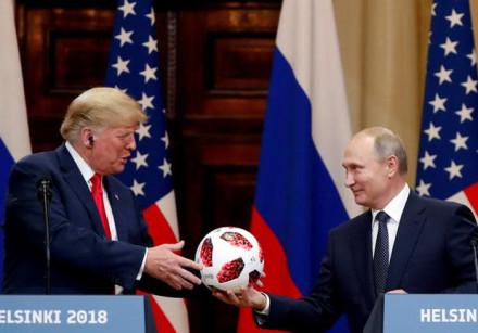 U.S. President Donald Trump receives a football from Russian President Vladimir Putin