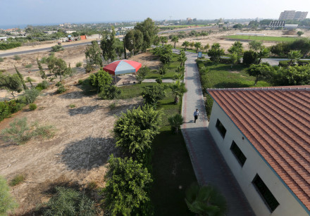 A Palestinian security guard walks at a university in Khan Younis in the southern Gaza Strip August