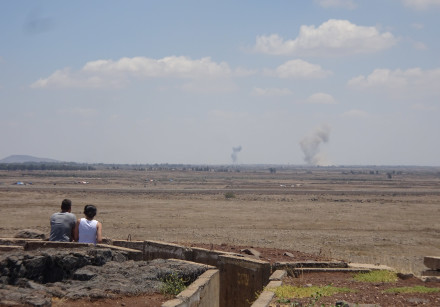 A couple watches the fighting in Syria from Tel Saqi, July 2018