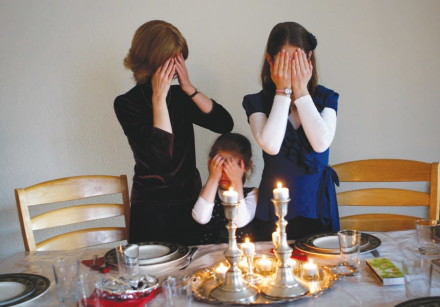 MEMBERS OF the Nogradi family light candles for Shabbat in their home in Budapest