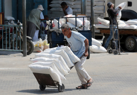 A Palestinian man pushes a cart with bags of flour at an aid distribution center run by UNWRA.
