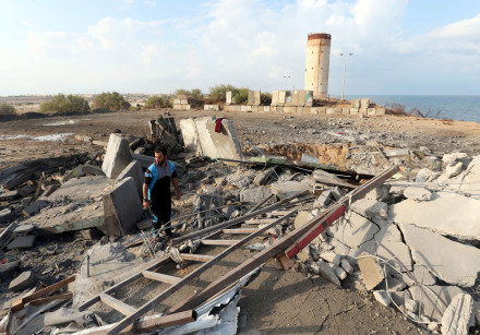 A Palestinian man inspects the scene of an Israeli air strike on a Hamas security forces site in the