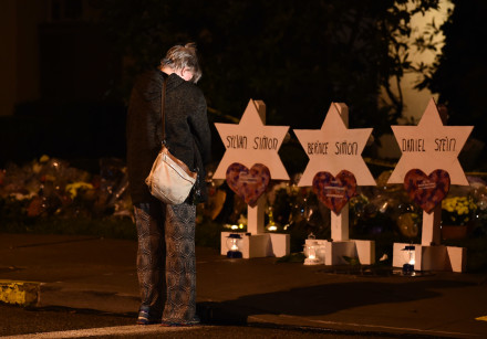 A woman bows her head in front of a memorial on October 28, 2018, at the Tree of Life synagogue