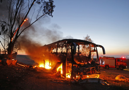 A picture taken on November 12, 2018 shows a bus set ablaze after it was hit by a rocket