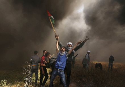 Palestinian demonstrators shout during clashes with Israeli troops at a protest