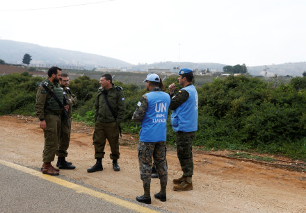 Israeli soldiers speak to UN peacekeepers (UNIFIL) near the border with Lebanon, in the town of Metu