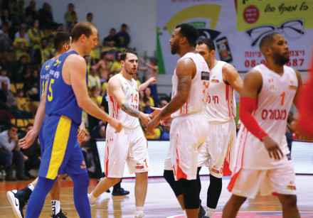 Ironi Ness Ziona players (in white) celebrate their 83-81 victory over Maccabi Tel Aviv in Basketbal