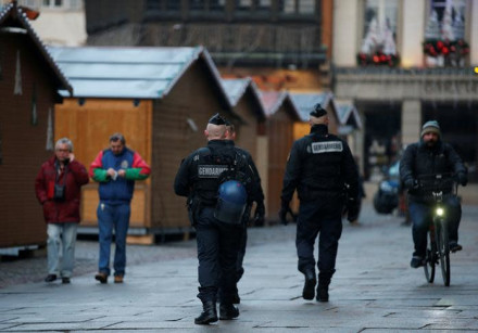 French Gendarmes patrol past wooden barracks shops after a shooting in Strasbourg, France