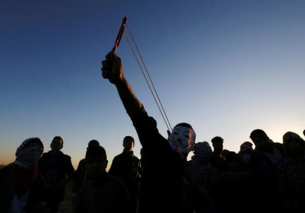 A Palestinian demonstrator uses a slingshot to hurl stones at Israeli troops.