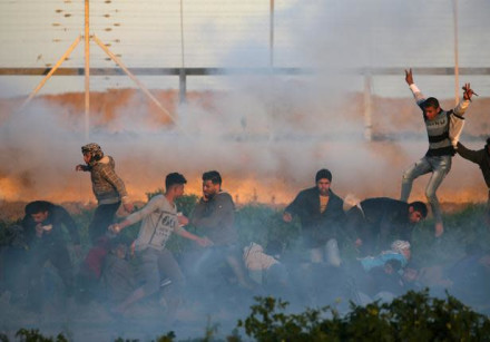 Palestinians run for cover from tear gas fired by Israeli forces during a protest