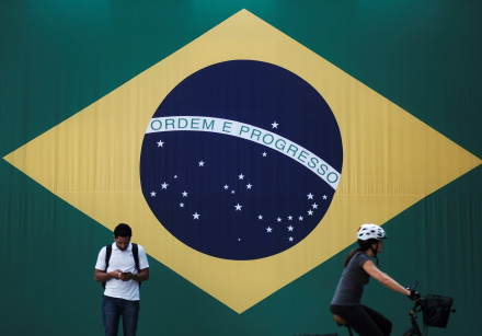 A man checks his mobile phone as a woman riding a bike passes next to a big Brazilian flag in Sao Pa