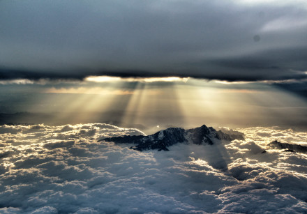 """Sun penetrating the clouds above the mountains near Chengdu, China. """"It looks like Genesis to me,"""" s"""