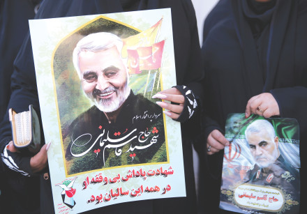 WOMEN HOLD pictures of Iranian Maj.-Gen. Qasem Soleimani during a funeral procession and burial at h