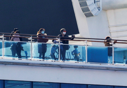 Passengers and children stand on the desk of the cruise ship Diamond Princess, as the vessel's passe