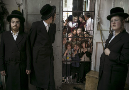 Schoolchildren stand in the doorway and watch as ultra-Orthodox Jews prepare matza in Bnei Brak near