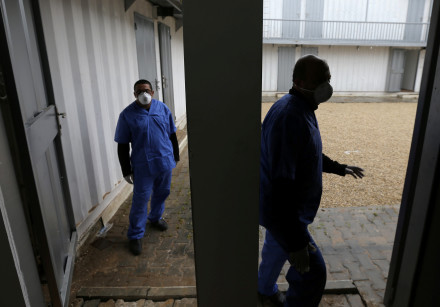 Palestinian health workers wearing protective masks walk in a quarantine zone installed by the minis