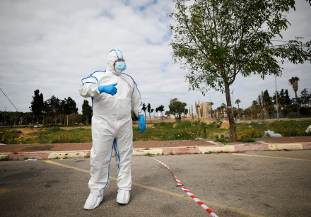 A paramedic wearing a protective suit stands near a special polling station set up by Israel's elect
