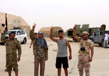 Members of Libya's internationally recognised government flash victory signs after taking control of