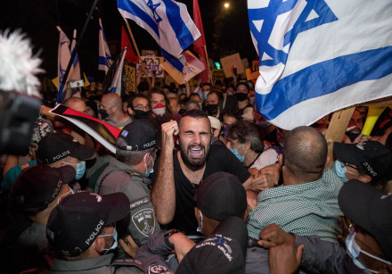Israeli police officers scuffle with demonstrators during a protest against Israeli prime minister B