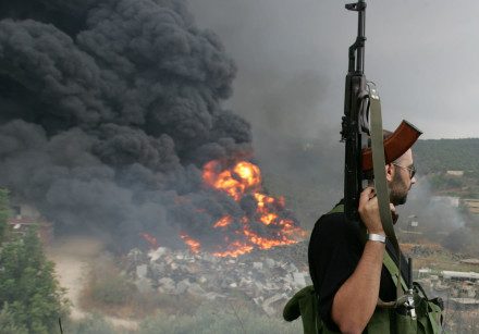 A Lebanese Hezbollah guerrilla looks at a fire rising from a burning object in a Beirut suburb, Leba
