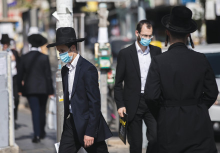 Ultra-Orthodox residents walk through of the Mea She'arim neighborhood of Jerusalem, August 2020