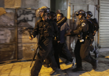 Israeli police officers detain a Palestinian suspected of throwing stones during clashes