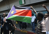 Migrants dance with flag of South Sudan
