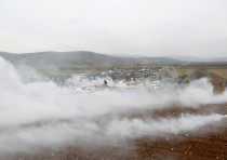 Protesters run away from tear gas