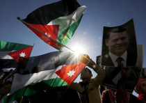 Protesters hold up pictures of Jordanian King Abdullah and pilot Muath al-Kasaesbeh