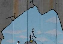 A Palestinian boy walks past a drawing by British graffiti artist Banksy