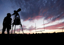 A woman looks through a telescope  the evening before a solar eclipse in Madras, Oregon, U.S.