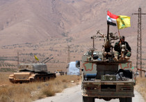 Hezbollah and Syrian flags flutter on a military vehicle in Western Qalamoun, Syria August 28, 2017.