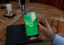 An employee shows the logo of ride-hailing company Careem on his mobile in his office in the West Ba